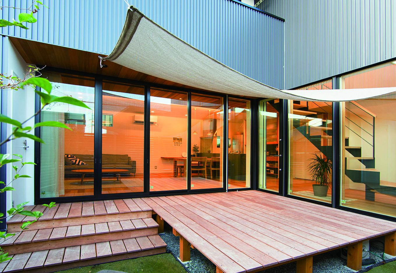大きなウッドデッキがL字型の家を繋ぐ。中庭の植栽は、ご主人自らが手掛ける