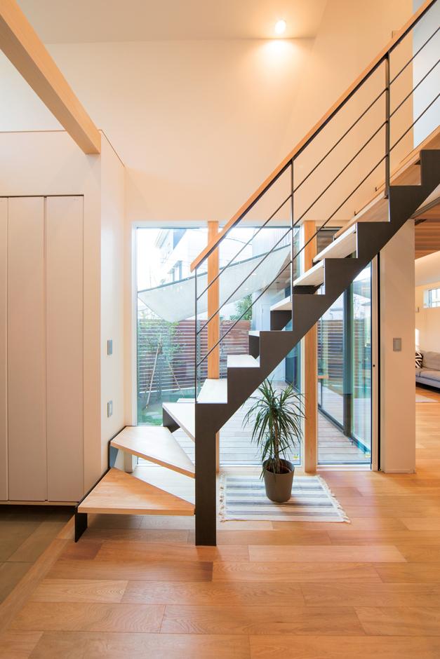 玄関ホールも中庭に面してガラス張りに。圧迫感のないスケルトン階段を採用