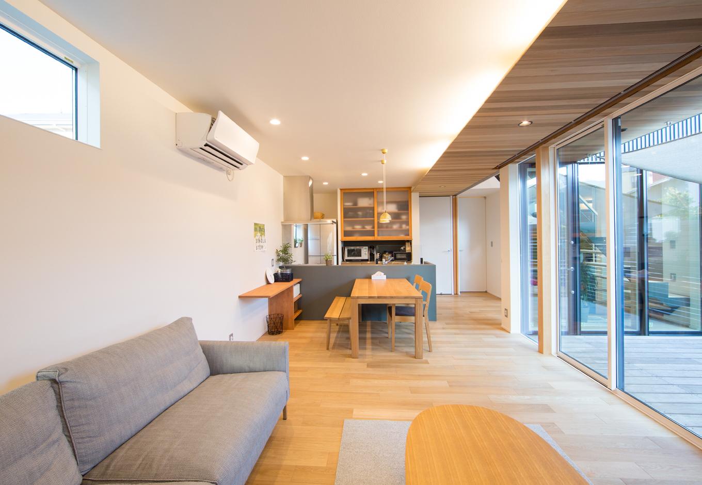 リビングからキッチンまでを一直線に繋げ、空間を広く見せている。中庭の軒から伸びる天井に仕込まれた間接照明も、癒しになる空間