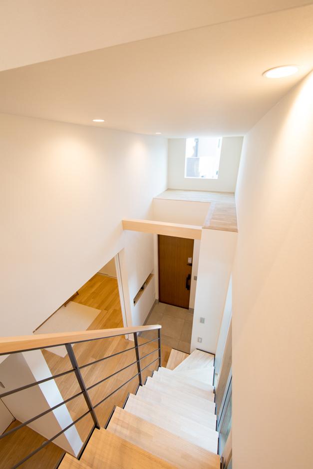 TENアーキテクツ 一級建築士事務所【デザイン住宅、狭小住宅、建築家】玄関から階段にかけて、吹き抜けのような空間を設けた。玄関上部にはフィックス窓を設けてあるので、日中は外からの光が入る明るい空間に