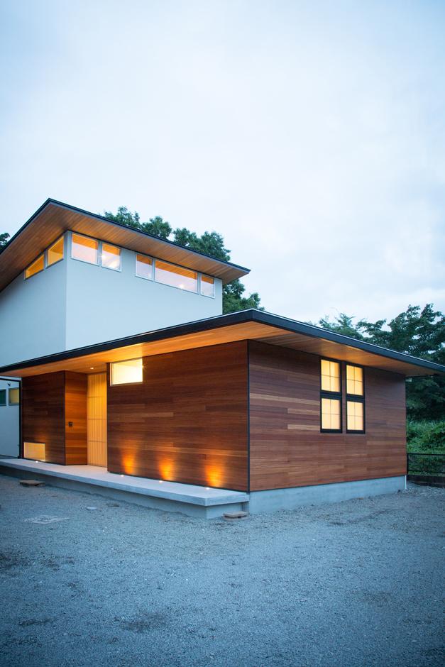 TENアーキテクツ 一級建築士事務所【デザイン住宅、夫婦で暮らす、建築家】木と塗り壁の風合いが優しい印象の外観。窓の配置によって、夜、室内から漏れる明かりもデザインの一部に取り込む。玄関の地窓や間接照明にもこだわりを感じる