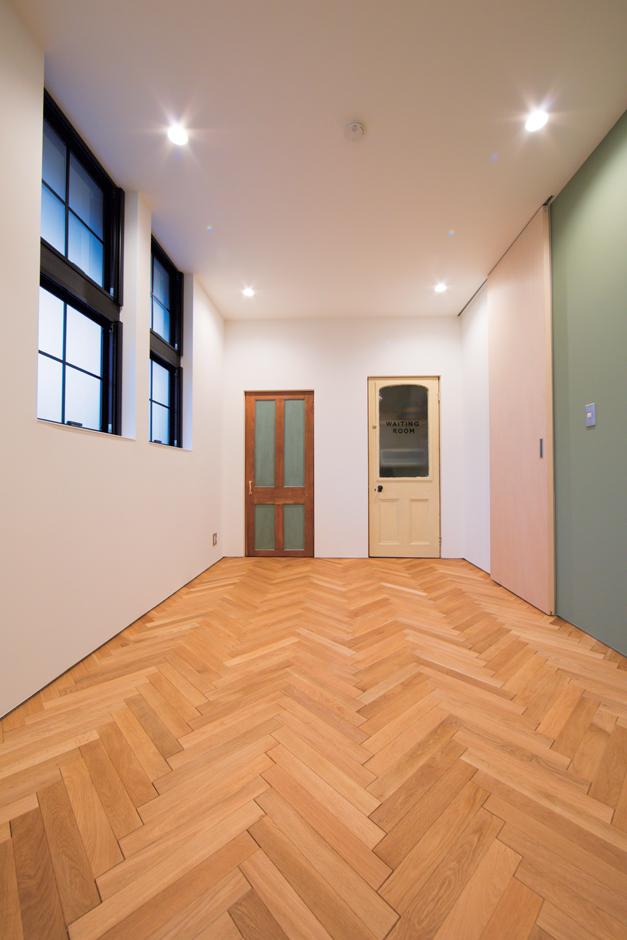 TENアーキテクツ 一級建築士事務所【デザイン住宅、夫婦で暮らす、建築家】ヘリンボーン床を採用し、レトロ感のある写真スタジオ。小窓や収納のドアは、撮影の際の背景をイメージして奥さまが手配したもの
