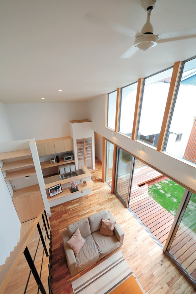 TENアーキテクツ 一級建築士事務所【デザイン住宅、ガレージ、建築家】吹き抜けと中庭に面した全面窓で、明るく開放感たっぷりのリビング。勾配天井と、それに沿うように傾斜の付いた窓が空間のアクセントになっている