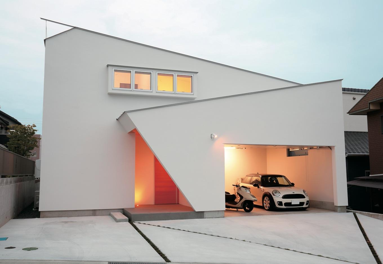 TENアーキテクツ 一級建築士事務所【デザイン住宅、ガレージ、建築家】家本体の大屋根と、玄関とガレージを覆う2枚の屋根がクロスする。スクエアな形状を部分的に巧みに切り取った、シンプルで個性的な外観