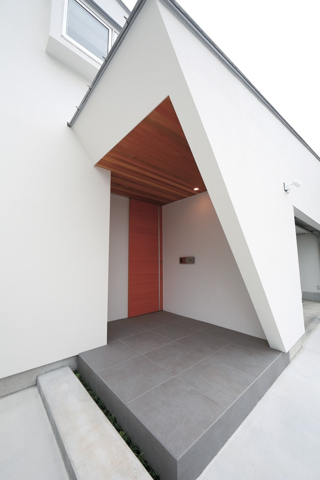 TENアーキテクツ 一級建築士事務所【デザイン住宅、ガレージ、建築家】屋根の対角に合わせて斜めに切り取った玄関ポーチの壁。レッドシダーの天井が壁の白さを際立たせる