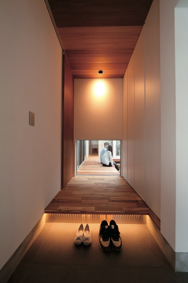 TENアーキテクツ 一級建築士事務所【デザイン住宅、ガレージ、建築家】玄関ホールの壁はガラスの地窓にし、中庭の緑と光を室内に取り込む