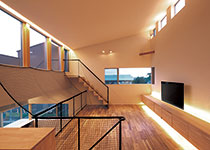TENアーキテクツ 一級建築士事務所【デザイン住宅、スキップフロア、建築家】リビングには勾配天井と、左下のダイニ ング、左上のバルコニーとの連続性により生まれた開放感。敷地の個性と周辺環境を踏まえた空間計画により、広さ以上の居心地がもたらされた。床には濃淡ある色合いが特徴のアカシア。 壁の塗りはテレビ背後の一面だけ櫛引きで仕上げ、落ち着きを添えた