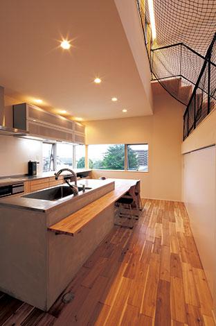 TENアーキテクツ 一級建築士事務所【デザイン住宅、スキップフロア、建築家】コンクリート製の造作キッチンがダイニングキッチンの主役。天 板のステンレスはキズが目立たないような仕上げが施されている。右手は蔵収納と室内ランドリースペース