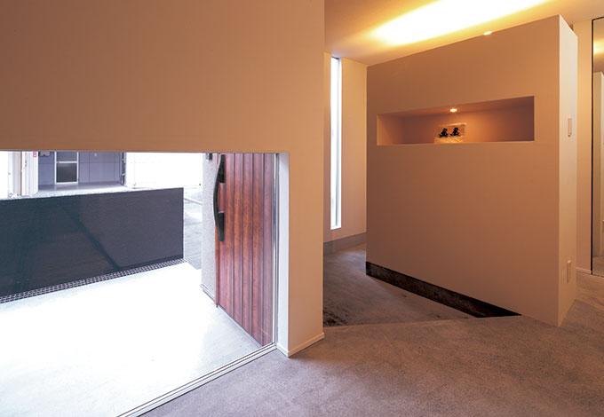 TENアーキテクツ 一級建築士事務所【デザイン住宅、スキップフロア、建築家】「店舗のような雰囲気にしたい」「空間として統一感が感じられるように」との要望から、玄関からホールにかけては土間の洗い出し仕上げに。壁の奥は可動棚を備えた家族用の玄関
