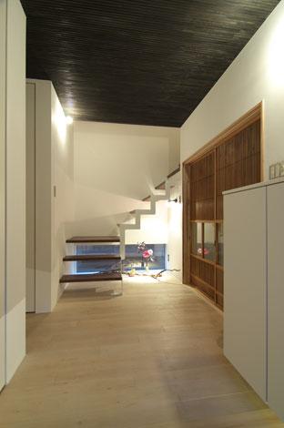 TENアーキテクツ 一級建築士事務所【二世帯住宅、ペット、建築家】階段には壁を作らず、玄関に開放感を持たせた。明かり取りの窓が、さらに空間に広がりを与えてくれる