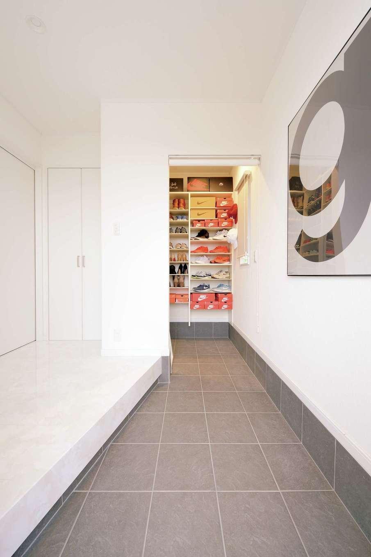 真っ白な壁と床に、三和土のグレーが映える玄関。奥の収納には、ご主人が集めているNIKEのスニーカーがずらり