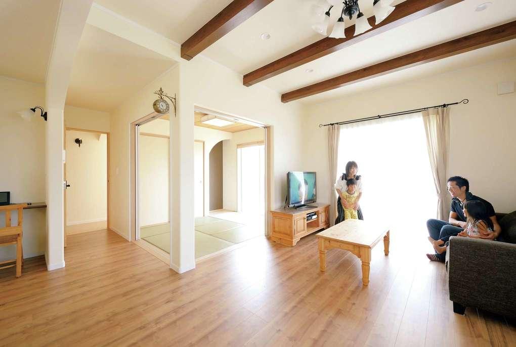 LDKと和室がワンフロアで繋がる開放的な空間。R壁や天井の梁をアクセントにして空間にメリハリをつけている。パイン材の家具が南欧風の家にぴったり