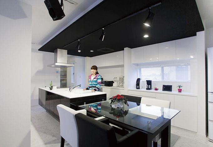 アイフルホーム焼津店 (三住建設)【デザイン住宅、夫婦で暮らす、ガレージ】アイランドキッチンとダイニングテーブルを横並びにレイアウトすることで、配膳もラクラク。みんなが集まっている場所で料理ができる、開放的で気持ちのいいスペースになった。奥さまがどうしても欲しかったアイランドキッチン。スポットライトの照明は光の演出だけでなく、手元を明るく照らしたいときにも便利