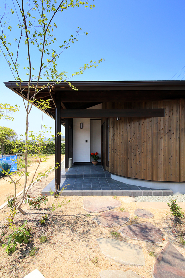 となりの建築工房【自然素材、省エネ、間取り】杉板を貼ったR型の壁に、大屋根を組み合わせた趣きあふれる玄関ポーチ。Rの造作が同社の施工技術の高さを表す