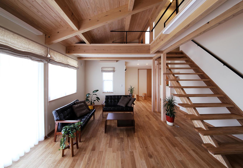 となりの建築工房【自然素材、省エネ、間取り】縦の空間を広くとった勾配天井と、スリット階段の組み合わせで開放的に設えたリビング。南と西に窓を設け、採光も抜群