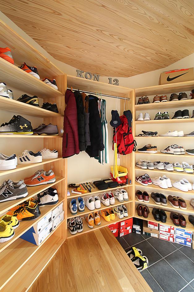となりの建築工房【自然素材、省エネ、間取り】ご主人自慢のシューズコレクションを展示するR壁内側のシューズクローク。ご主人の靴のサイズに合わせて棚の奥行きを設定した