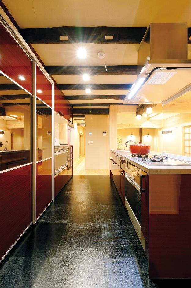 戸田工務店【和風、二世帯住宅、間取り】黒い漆塗りの麻の床材にワインレッドのシステムキッチンが映える。キッチンから半歩動けば玄関を望め、帰宅する家族に声をかけることができる