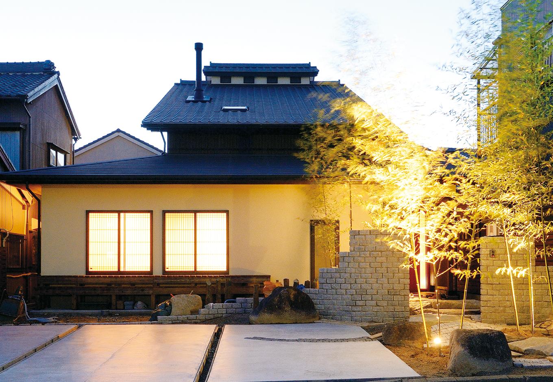 戸田工務店【和風、二世帯住宅、間取り】竹林が彩る石畳のアプローチ。わざと起伏を付けることで実際以上の奥行き感を演出。エアパス工法の特徴でもある腰屋根がアクセントに