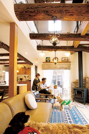 戸田工務店【輸入住宅、趣味、インテリア】吹抜けの古材の梁には、奥さまの趣味であるアンティークのペンダント照明を吊るしてある。2種類の照明をシンメトリーに配置し、室内にバランスよく灯りをもたらすよう配慮。古材の古びた木肌と淡い光を放つノスタルジックな照明が絶妙にマッチして、室内を味わい深く演出している