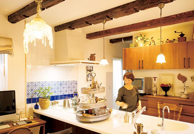 戸田工務店【輸入住宅、趣味、インテリア】天井の古材の梁の質感がアンティーク照明によく似合うキッチン空間。壁面にはスペイン製のタイルを使用。なかなか数がそろわない稀少品を『TODA』が調達したもの。奥さまのアイデアでブリキのプランターを食器入れに活用したら、キッチンがいっそうオシャレな雰囲気に!背後の棚の上には、設計の楠さんの手描きパースが大切に飾られている
