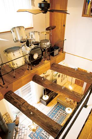 戸田工務店【輸入住宅、趣味、インテリア】吹抜けからLDKを臨む。太い古材の梁の上に施されているガイシを使った配線が、昭和の暮らしを彷彿とさせる。キャットウォークにはご主人のドラムが飾られており、まるで空中ステージのよう