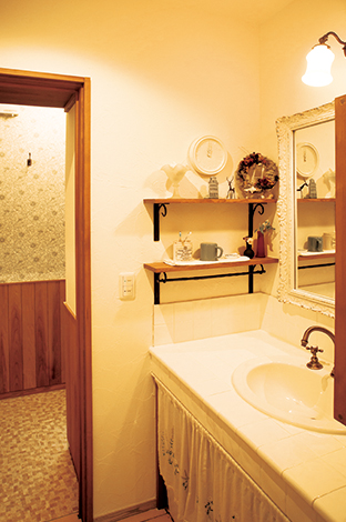 戸田工務店【輸入住宅、趣味、インテリア】玄関を上がってすぐ左手に設けた洗面コーナーは、白いタイルと白い木枠の鏡を組み合わせ、フレンチアンティーク風に演出