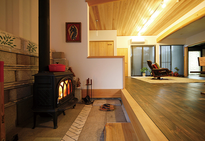 戸田工務店|昔の家でよく見かける勝手口を活かして作られた土間空間。T 邸では薪ストーブを据え、広いLDKの中のもう1つの小さなリビ ングに。土間に敷かれ た天然石が独特な味わいを醸し出している