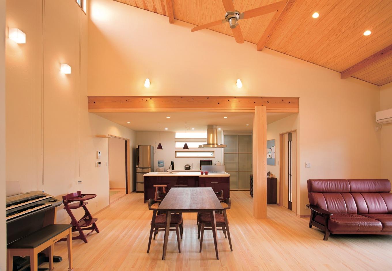 新栄住宅【自然素材、間取り、平屋】勾配天井でより広く感じられるLDK。TVボード、リビングテーブル、リビングチェスト、ダイニングセット、書斎の椅子、スツールもすべて塩澤社長が選び抜いてコーディネートした「シンエイスタイル」。ヒノキの床の質感に対比させて、ウォールナットでまとめた。奥さまの好きな赤がナチュラルな空間の差し色になっている