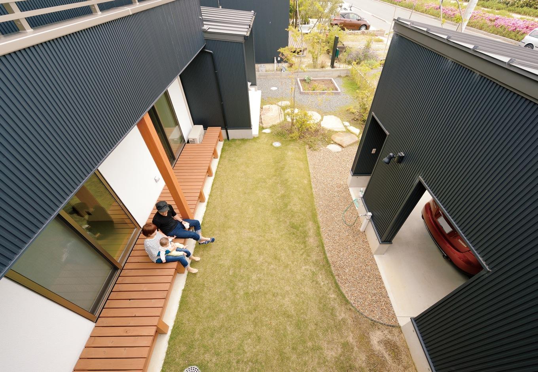 新栄住宅【自然素材、間取り、ガレージ】ガレージを別棟にしたことによって生まれた中庭。深い軒下のデッキは、 お茶を飲んだり、日向ぼっこをしたり、 楽しみ方が広がるアウトドアリビング