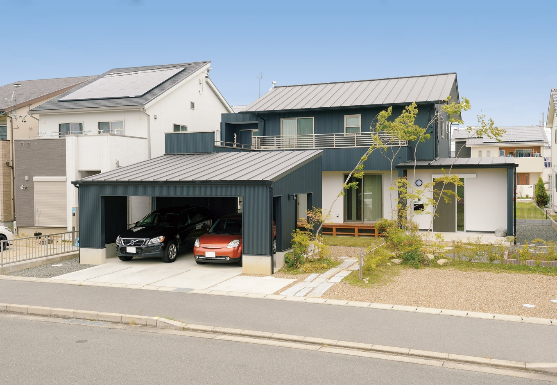 新栄住宅【自然素材、間取り、ガレージ】ブラックガルバリウムのシャープな外観。ガレージと母屋が中庭を挟んでつながっている