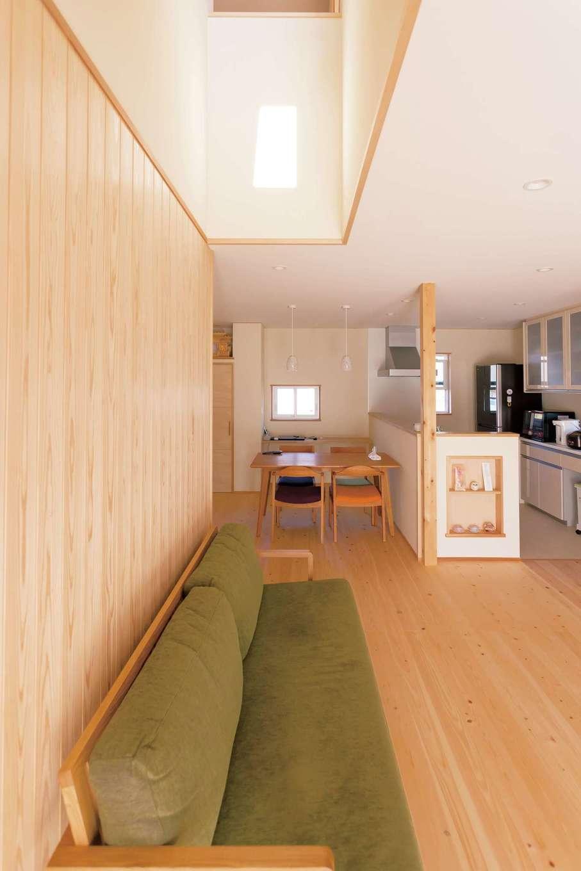 ソファの背もたれが当たって壁に傷が付くのを防ぐため、無垢の杉板を貼ってアクセントウォールに。吹抜けを通して2階とのコミュニケーションもスムーズ