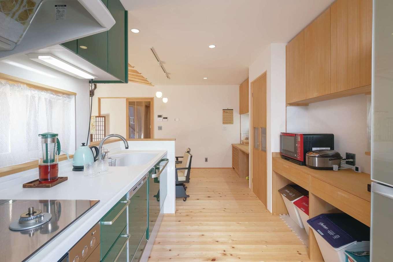 新栄住宅【収納力、和風、間取り】作業スペースの広いキッチン。パネルは奥さまの大好きなグリーンをセレクト。玄関からサニタリー、ダイニング、キッチン、勝手口、ウッドデッキへとノンストップでつながる動線が共働き・子育てママの家事時間を大幅に短縮する