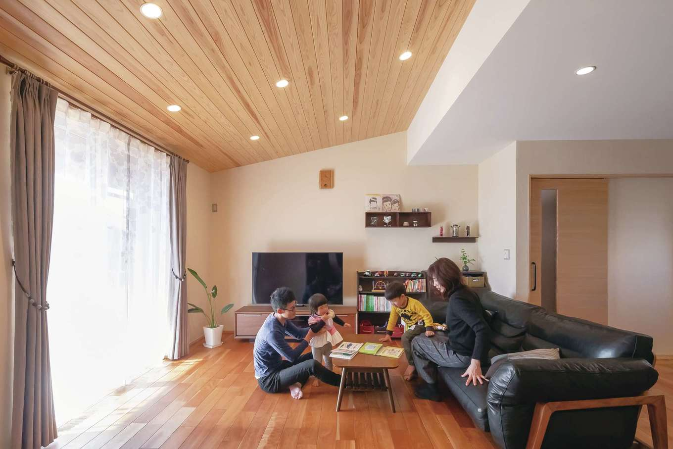 新栄住宅【デザイン住宅、子育て、間取り】気持ちいい風が通り抜ける22.3畳のLDK。リビングの勾配天井に無垢板を貼り、アクセントをつけた。飾り棚にグリーンや小物を飾って季節感を演出