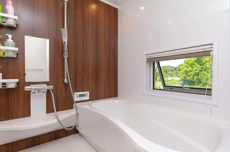 新栄住宅【自然素材、間取り、平屋】お風呂好きなご主人のリクエストに応えて、湯船に浸かりながら庭の借景を楽しめるように窓をしつらえた。アパート時代はお風呂嫌いだった長男が長風呂になったのも納得!