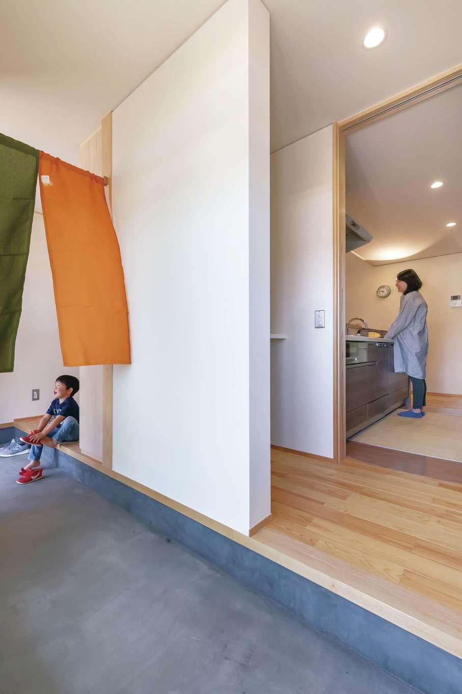 新栄住宅【自然素材、間取り、平屋】リビングとキッチンの2方向にアクセスできる土間玄関。キッチン、洗面脱衣室、浴室、デッキへと一直線につながる