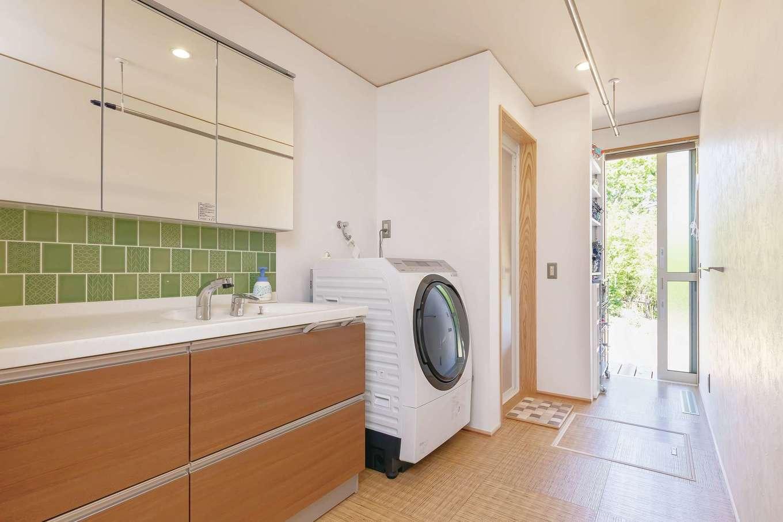 新栄住宅【自然素材、間取り、平屋】室内干しスペースもある広い洗面脱衣室。奥の引戸を開けると洗濯物を干せるデッキがある
