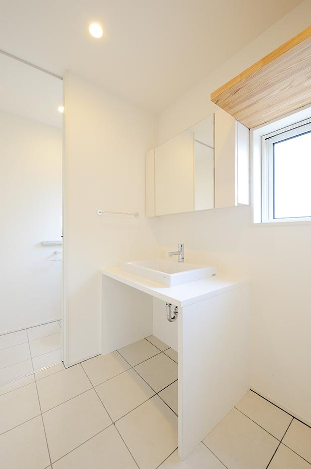 奥にあるトイレを含め、洗面スペースはすべて白で統一。窓から柔らかな自然光が注がれ、清潔な印象が引き立つ
