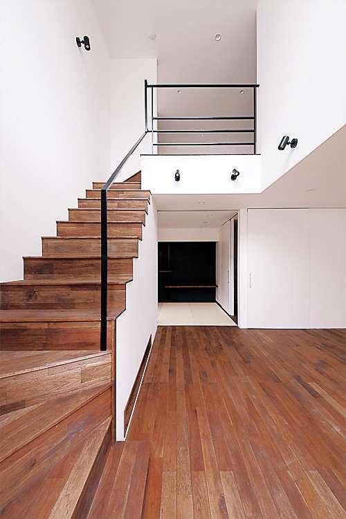 吹抜けの階段。手摺りのアイアンや無垢床がお互いの素材感を惹きたてる