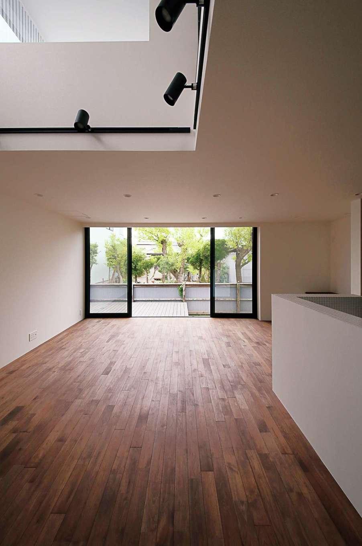 インフィルプラス【デザイン住宅、狭小住宅、間取り】建物をオーバーハングにし、当初は1階に設ける予定だった和室を2階に配置したことで、LDKのスペースを広々と確保。吹抜けや大窓、庭先のデッキが開放感を強調