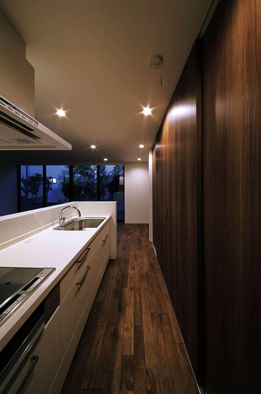 インフィルプラス【デザイン住宅、狭小住宅、間取り】キッチン背面の収納庫に冷蔵庫や電子レンジなども隠して収納し、生活感を排除