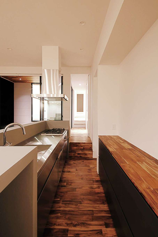 廊下奥のステップを上がると、水回りや個室がある。キッチンはアイランド式にて家事楽動線に