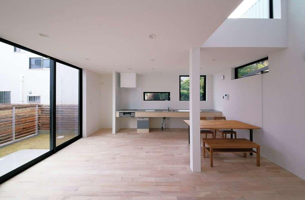 インフィルプラス【デザイン住宅、収納力、間取り】掃出し窓4枚分の大開口と吹抜けによってコンパクトでありながらも開放感溢れる空間を実現。白を基調とした内装がより広さを強調している