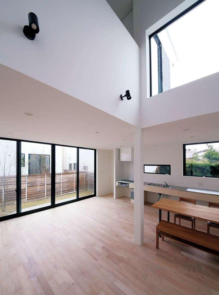 インフィルプラス【デザイン住宅、収納力、間取り】LDKには吹抜けがあり、高窓からメープルの無垢材の床に柔らかな陽光がたっぷりと降り注ぐ