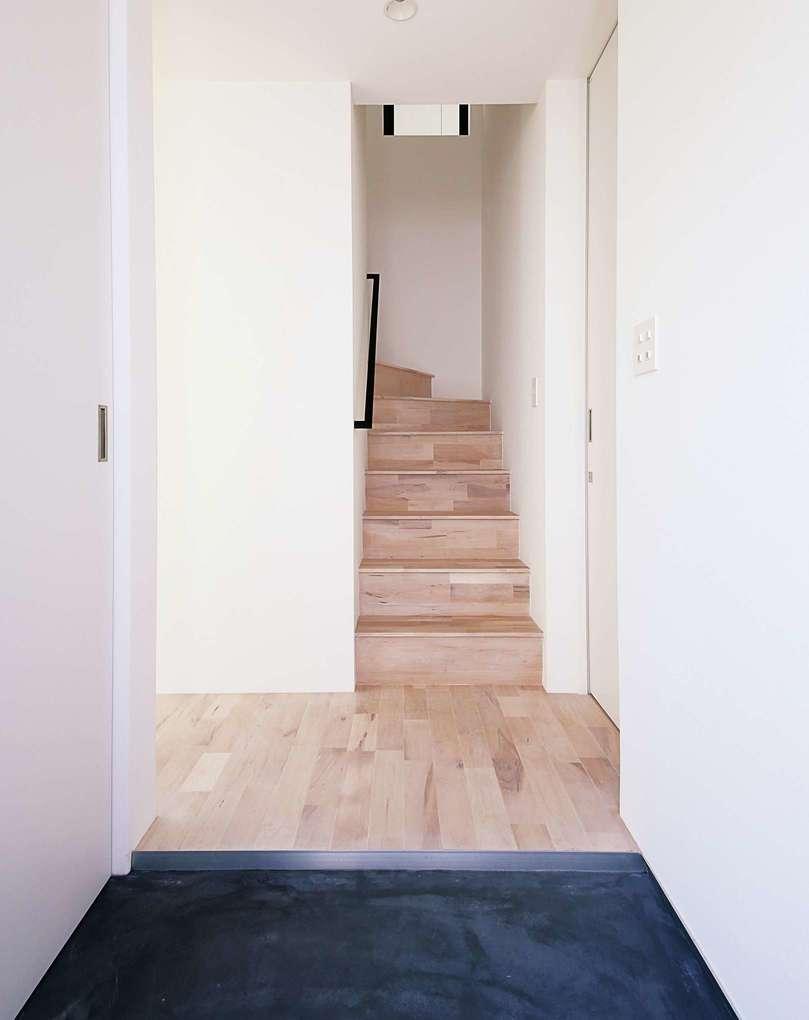 インフィルプラス【デザイン住宅、収納力、間取り】白を基調としたナチュラルテイストの内装にモルタルの黒い土間が映える玄関。左手には土間収納を設けてある