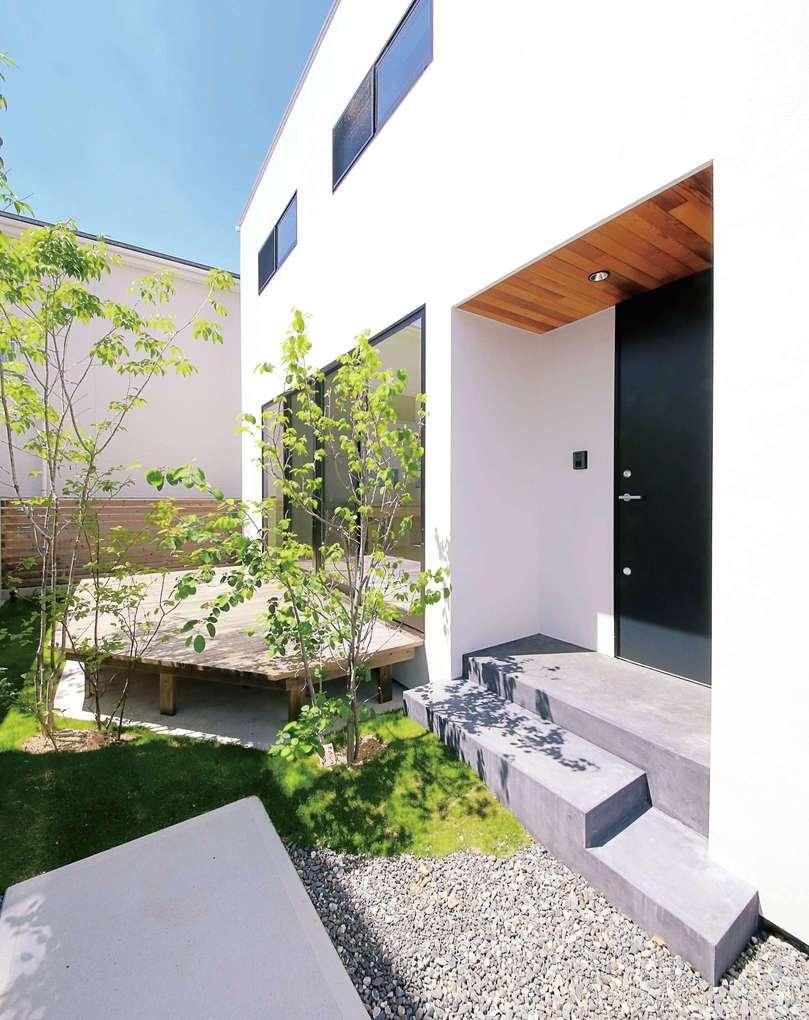インフィルプラス【デザイン住宅、収納力、間取り】建物の東側に設けたアプローチを進むと、横長の玄関ポーチがある。その奥には庭と広いデッキが見える