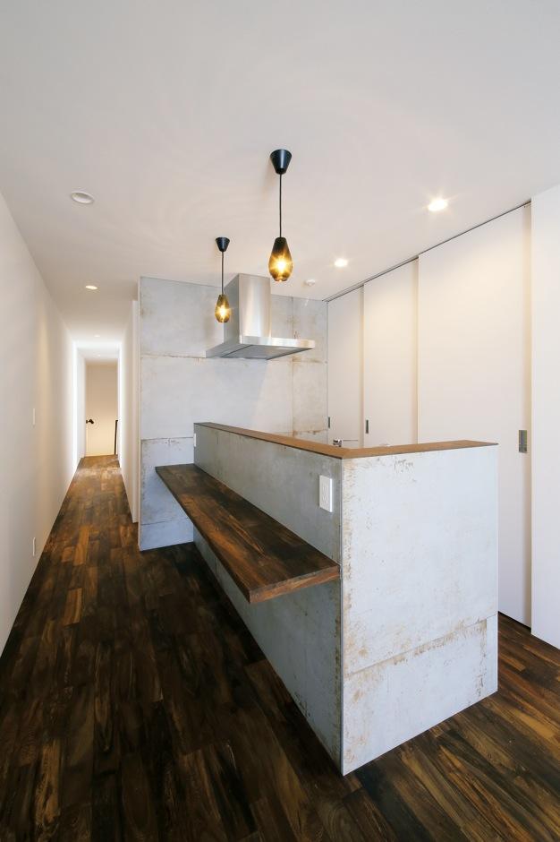 インフィルプラス【デザイン住宅、狭小住宅、インテリア】オープンキッチンのカウンターには床材と同じ鉄刀木の無垢材を使用。腰壁は汚れがつきにくい大判のタイル仕上げ