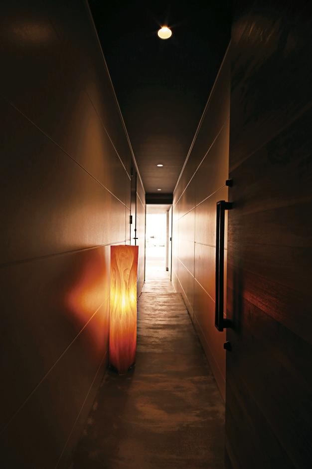 インフィルプラス【デザイン住宅、狭小住宅、インテリア】ガレージから玄関へといざなわれるような奥行き感と、ほの暗い空間に灯した照明が趣きを醸し出す通し土間