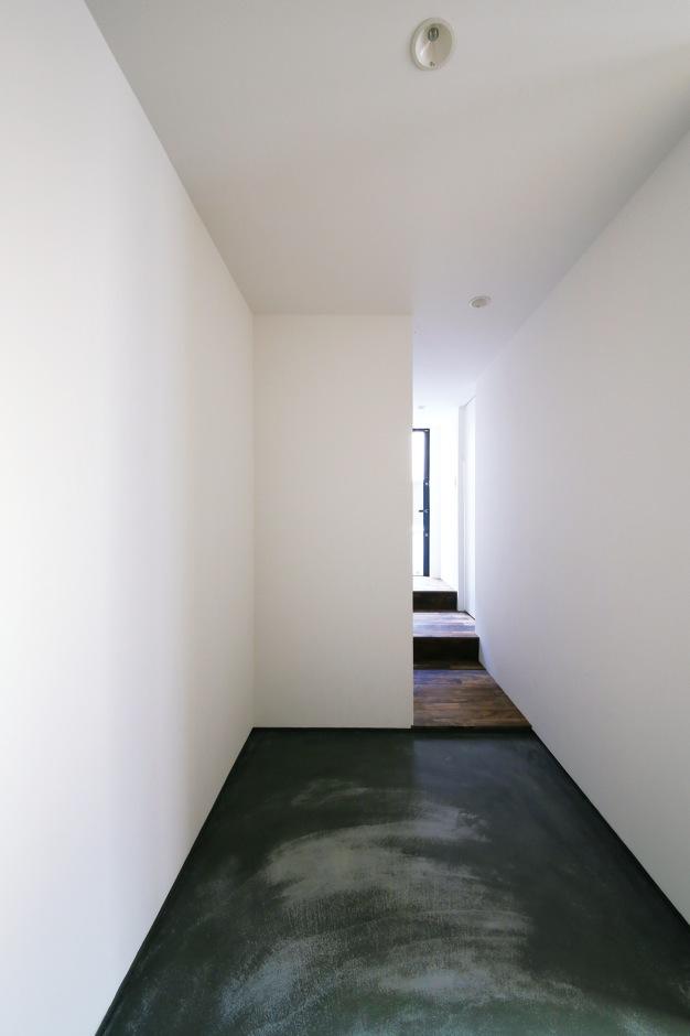 白い壁と天井、そして墨入りのモルタルの土間がおりなす玄関は洗練されたモノクロームの世界