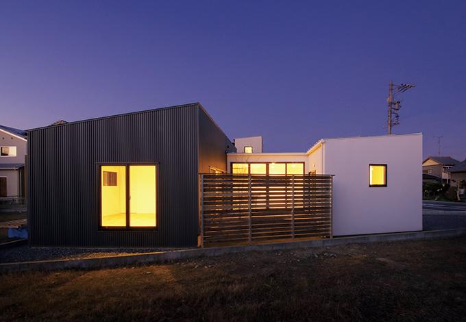 インフィルプラス【デザイン住宅、狭小住宅、平屋】南面から眺めた夜の外観。パティオの前にはフェンスを設け、外部からの視線を遮っている。室内から外を眺めた時も、隣家が視界に入らないようにフェンスの高さが工夫されている