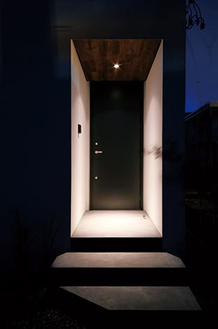 モルタルの床と黒いドア、無垢板張りの天井で構成されたスタイリッシュな玄関ポーチ